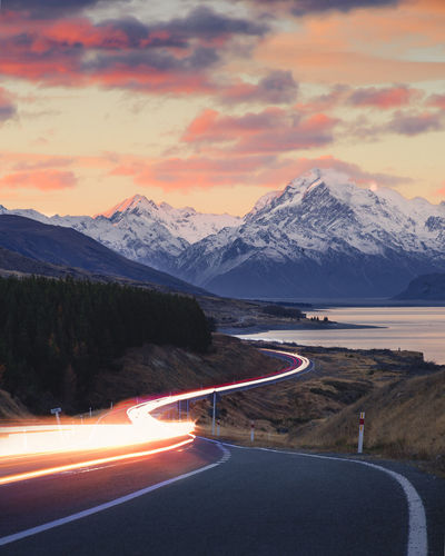 Beauty In Nature Cloud - Sky Direction Environment Landscape Lighttrails Long Exposure Mode Of Transportation Mountain Mountain Range Nature No People Road Scenics - Nature Sign Sky Snow Snowcapped Mountain Sunset The Way Forward Transportation Winter