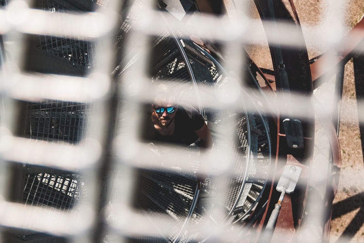 Man standing on spiral staircase seen through metal grate