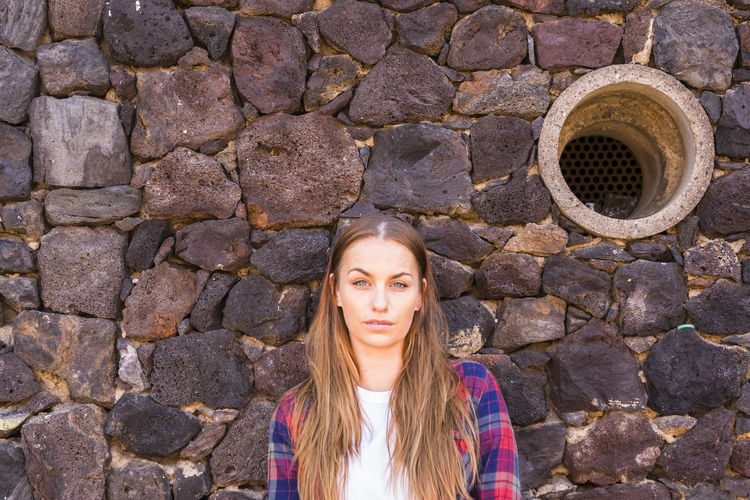 Portrait of young woman standing against stone wall