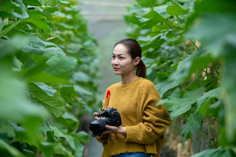 Young woman holding camera while standing amidst plants