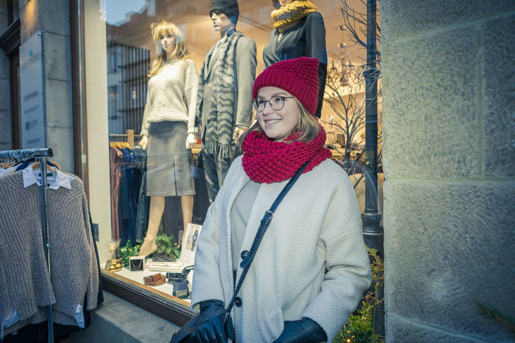 Smiling woman looking away while standing by clothing store