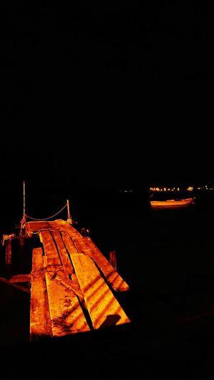 Illuminated lighting equipment on beach against clear sky at night