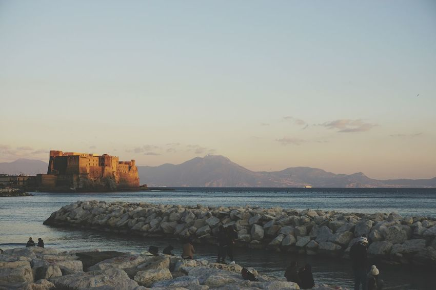Sunset in Naples Sunset Naples, Italy Castel Dell'ovo Mountain Range In Background People Watching Sunset Sea And Sky Waterfront Evening Mood Sony A6000 Napoli Illuminated By The Sun Travel Destinations Tourist Attraction