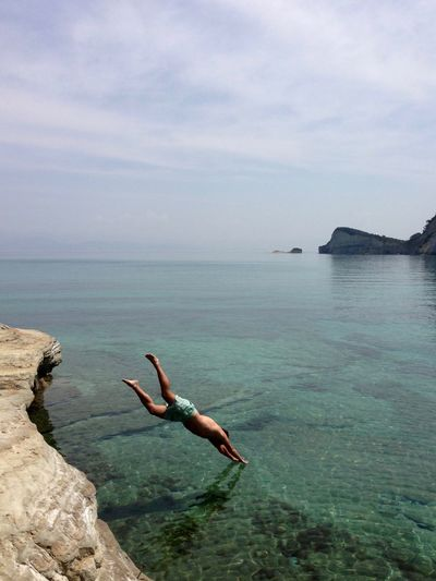 Shirtless man diving into sea against sky