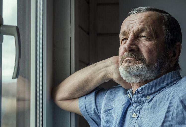 Portrait of man wearing hat at window