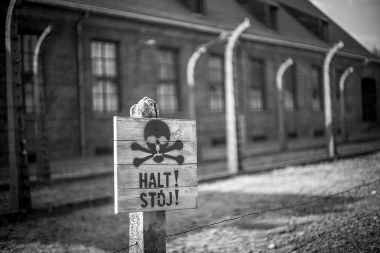 Auschwitz Auschwitz  Communication Text Focus On Foreground Architecture Western Script Sign No People Built Structure Day Representation Building Exterior Script Outdoors Human Representation Art And Craft Non-western Script Information Nature Paper