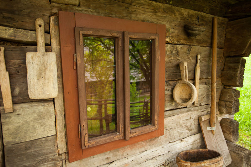 The inside of wooden house with a window is full of old living things such as boards and pots. Architecture Brick Built Structure Day Glass Grange No People Old Outdoors Rusty Tools Vintage Window