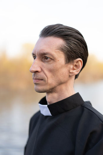 Handsome catholic priest portrait with collar Pastor Priest Collar Religion Religious  Belief Saint Father Beliver Man Men People person One Person Caucasian Middle Ages Catholicism Catholic Christianity Christian Faith Portrait Headshot Adult Well-dressed Focus On Foreground Males  Looking Away Day Looking Close-up Suit Formalwear Black Color Lifestyles Clothing Outdoors Contemplation