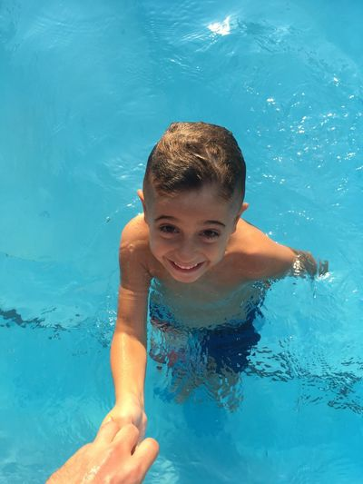 Cropped Hand Holding Smiling Boy In Swimming Pool