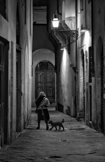 Florence Street By Night One Person Full Length Night Illuminated Real People Built Structure Lifestyles Mysterious Place Architecture Building Exterior City Winter Casting A Shadow Shadows & Light Shadows Black And White Monochrome The Best City In The World Florence Italy Florence Street Photography Travel Contrast Outdoors Street