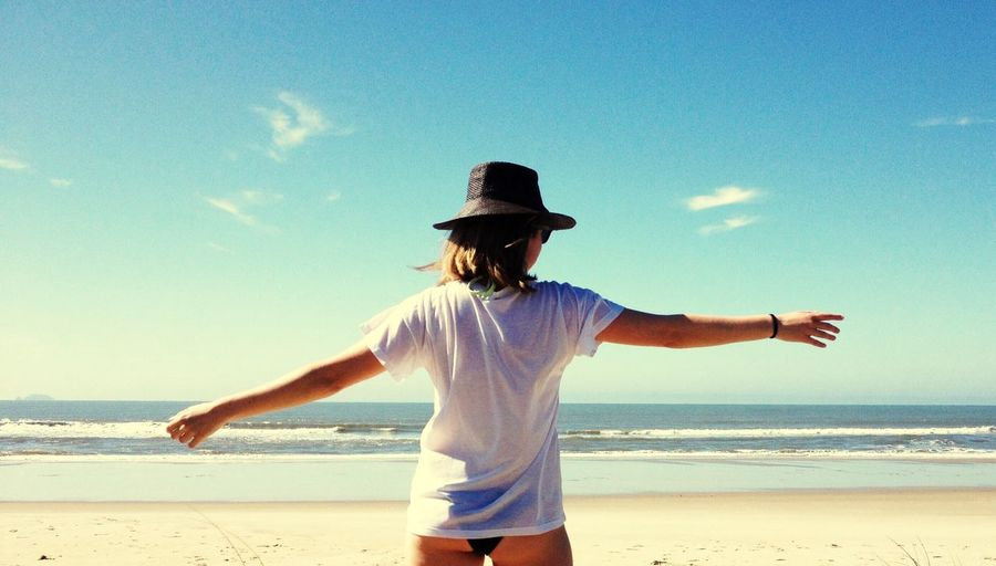 Woman With Arms Outstretched Standing On Beach Against Sky