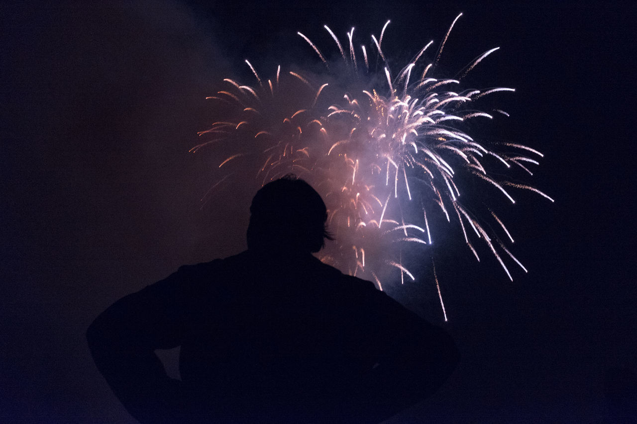 night, firework display, celebration, real people, rear view, firework - man made object, exploding, silhouette, long exposure, event, men, low angle view, arts culture and entertainment, lifestyles, sky, standing, leisure activity, firework, outdoors, illuminated, motion, one person, clear sky, people