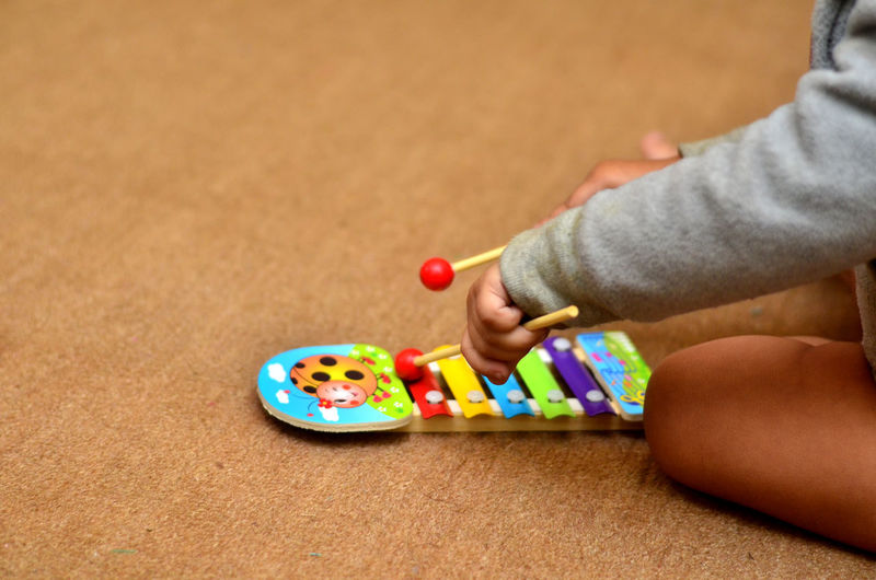 Midsection of child playing xylophone at home