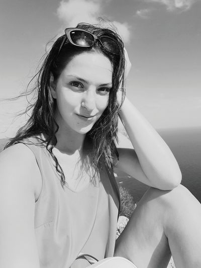 Portrait of young woman in sunglasses sitting against sea
