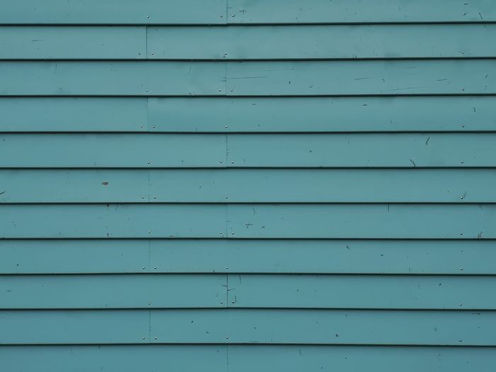 Closeup of a facade with turquoise colored horizontal facade panels. Architecture Architectural Detail Front View Turquoise Turquoise Colored Panels Panel Rivet Rivets Small Rivets Backgrounds Textured  Pattern Full Frame Protection Façade