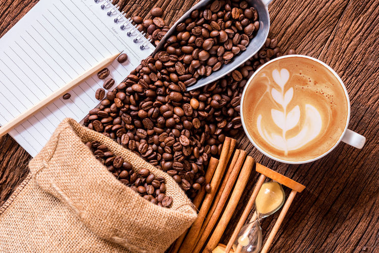 Directly above shot of roasted coffee beans with hourglass and coffee cup on wooden table