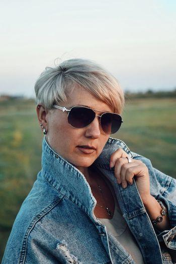 Portrait of woman wearing sunglasses on field