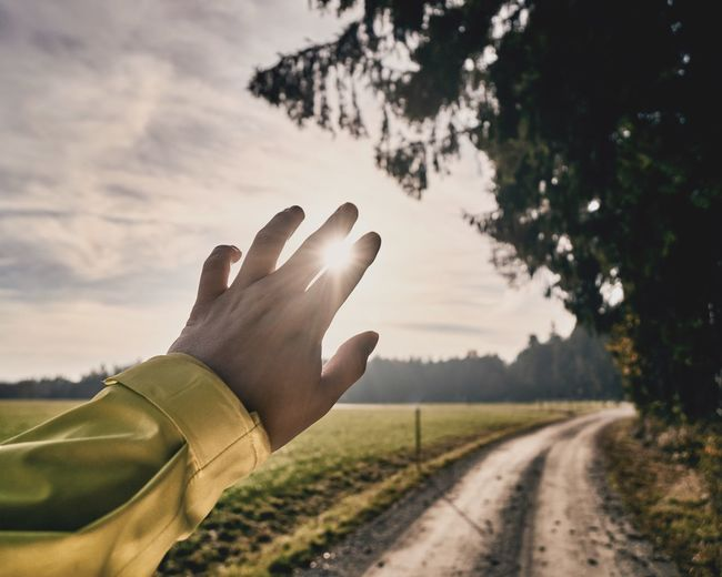 Close-up of hand gesturing against sky