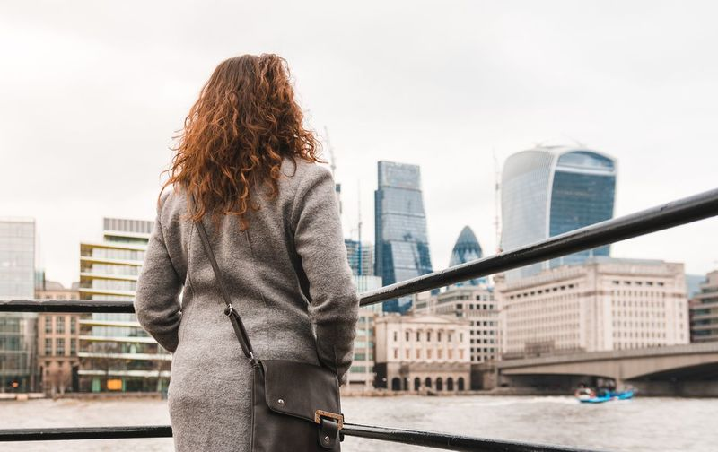 Rear view of woman standing by railing against river and buildings in city