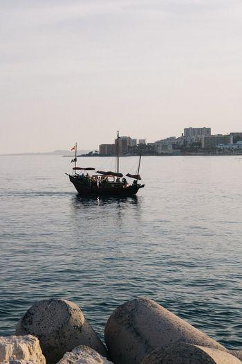 Sailboat sailing on sea against clear sky