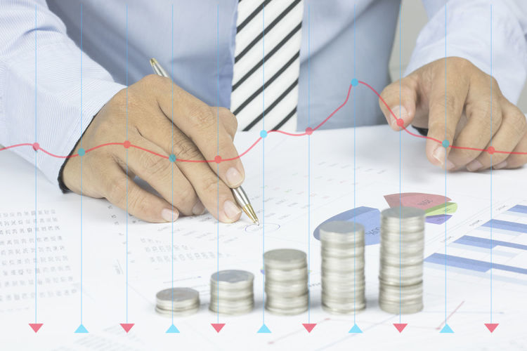 Digital composite image of line graphs against businessman analyzing data on desk in office