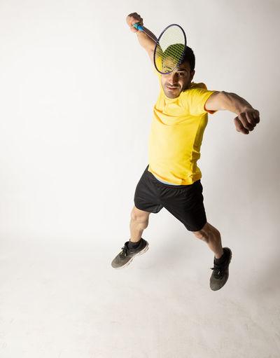 Full length of man jumping against white background