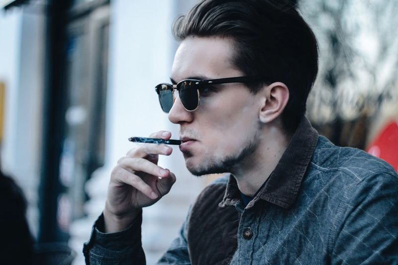 Sunglasses Only Men One Man Only Adult Adults Only Smoking - Activity Young Adult Headshot One Person Addiction Lifestyles Portrait One Young Man Only Leisure Activity People Casual Clothing Outdoors Day Young Men Men
