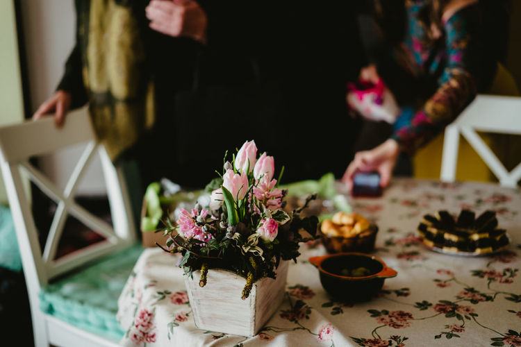 Midsection of woman holding flower bouquet on table