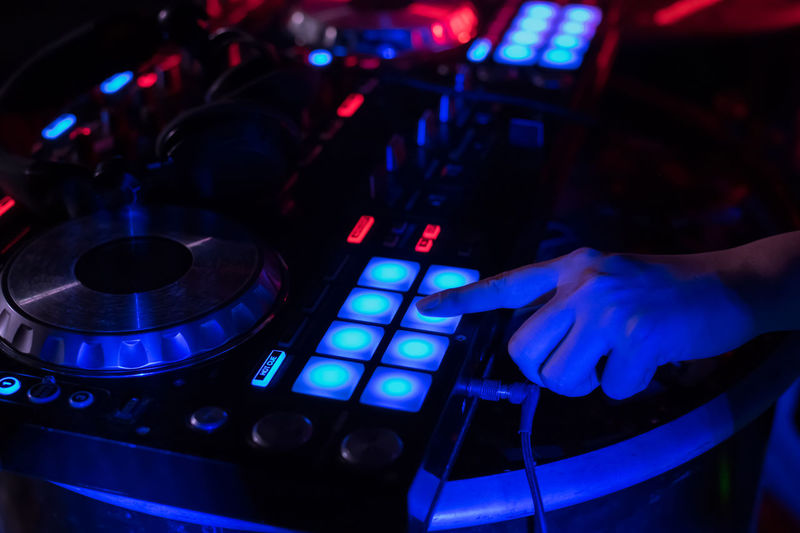 Close-Up Of Woman Playing Music On Audio Equipment In Nightclub