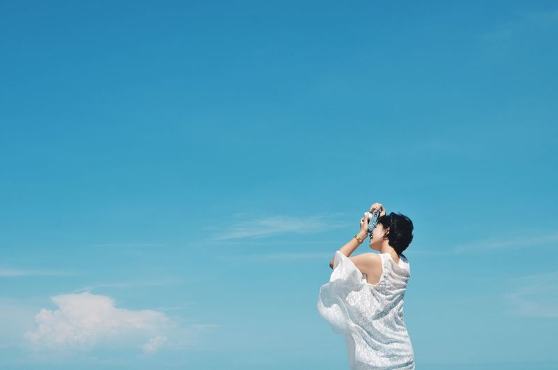 Low Angle View Of Woman Photographing Against Blue Sky