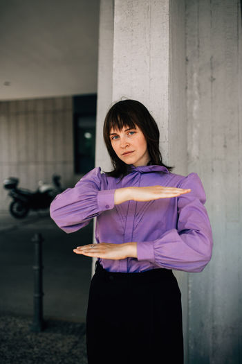 Portrait of young woman gesturing equal sign while standing against wall