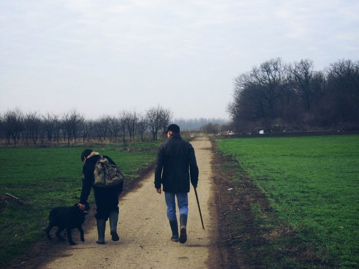 Rear view of men walking with dog on road amidst field against sky
