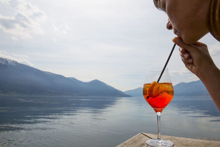 Woman drinking a spritz with a straw on the waterfront with mountain Adults Only Alcohol Color Copy Space Day Drinking Drinking Glass Headshoot Headshot Holding Human Hand Landscape Mountain Mountain Range One Woman Only Outdoors Part Of Human Body Sea Sky And Clouds Spritz Straw Sunny Water Waterfront Woman