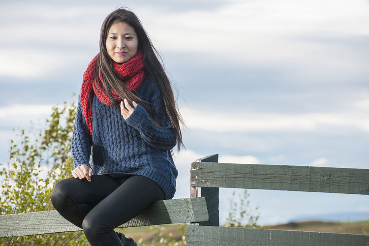 Portrait of woman sitting on railing against sky