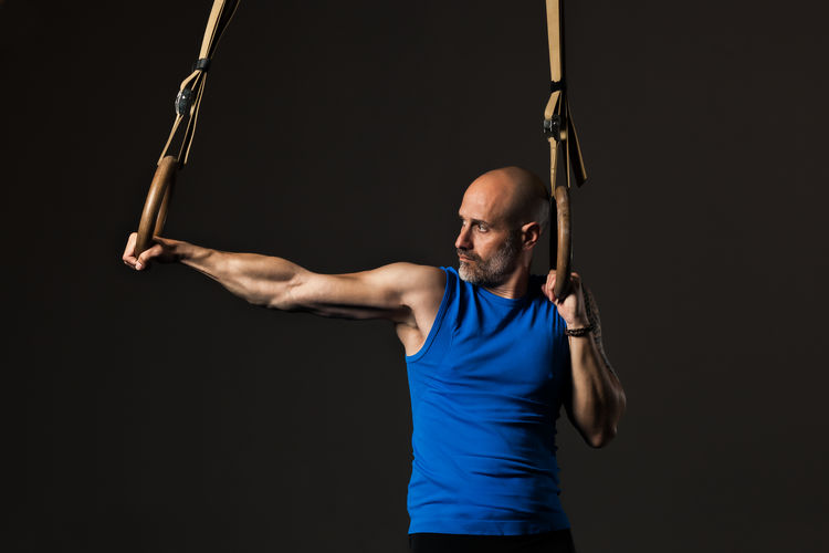 Confident man exercising against black background