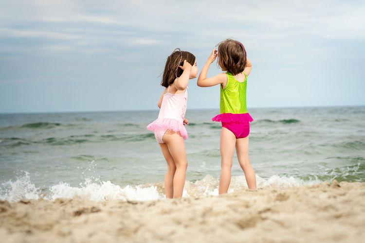 Rear view of siblings standing at beach
