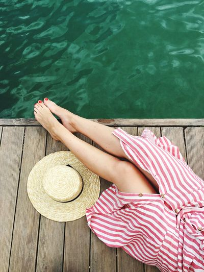 Low Section Of Woman Relaxing By Lake On Pier
