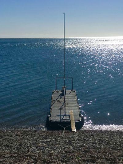 Fishing rod on sea against sky