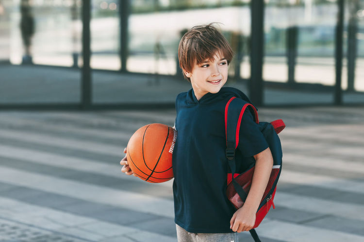 Portrait of smiling boy with ball in background