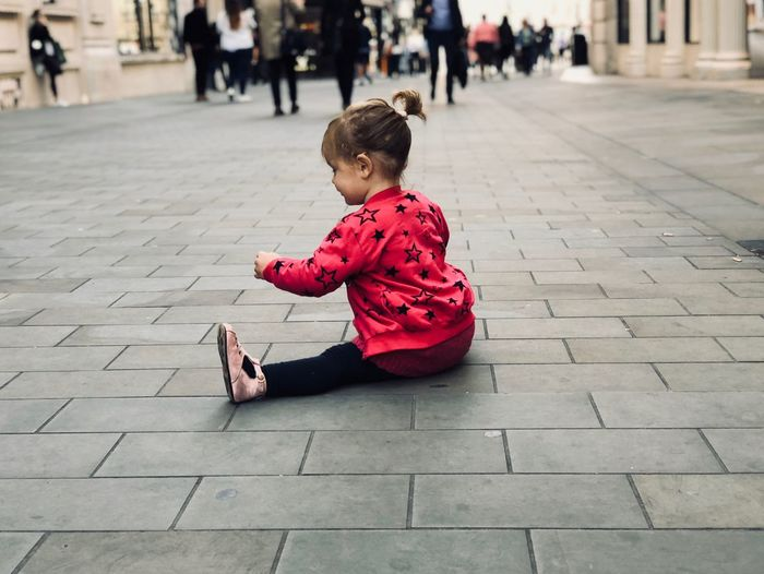 Girl sitting on footpath in city
