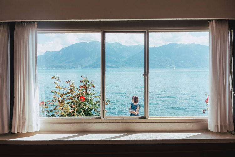 View of woman standing by lake seen through window