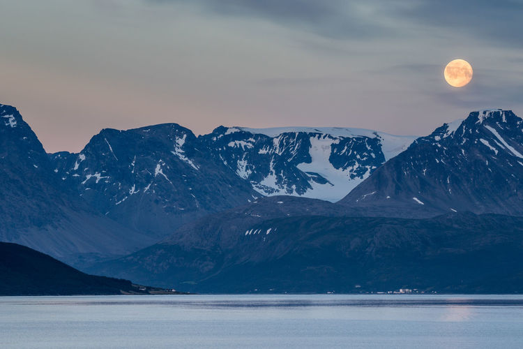 Scenic View Of Lake And Snowcapped Mountains Against Sky At Dusk