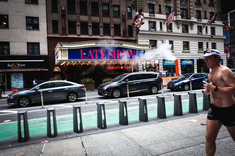 Full length of man on street against buildings in city