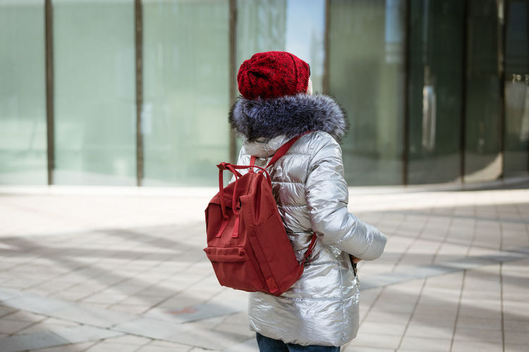 Happy young woman in winter jacket with backpack near building
