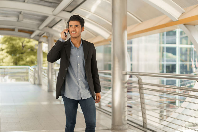 Portrait of young businessman standing at Outside Office and talking on smartphone. Asian Business man wear suit and handsome look. ASIA Attractive Building Business Young Airport Work Walking Using Urban Success Street Standing Smile Professional Portrait Place Phone Smart person People Outside Outdoor Office Modern Manager Male Looking Lifestyle Job Holding Day Corporate Confident  Communication City Casual Career Smart Phone Technology Man Day Time One Person Using Phone Mobile Phone