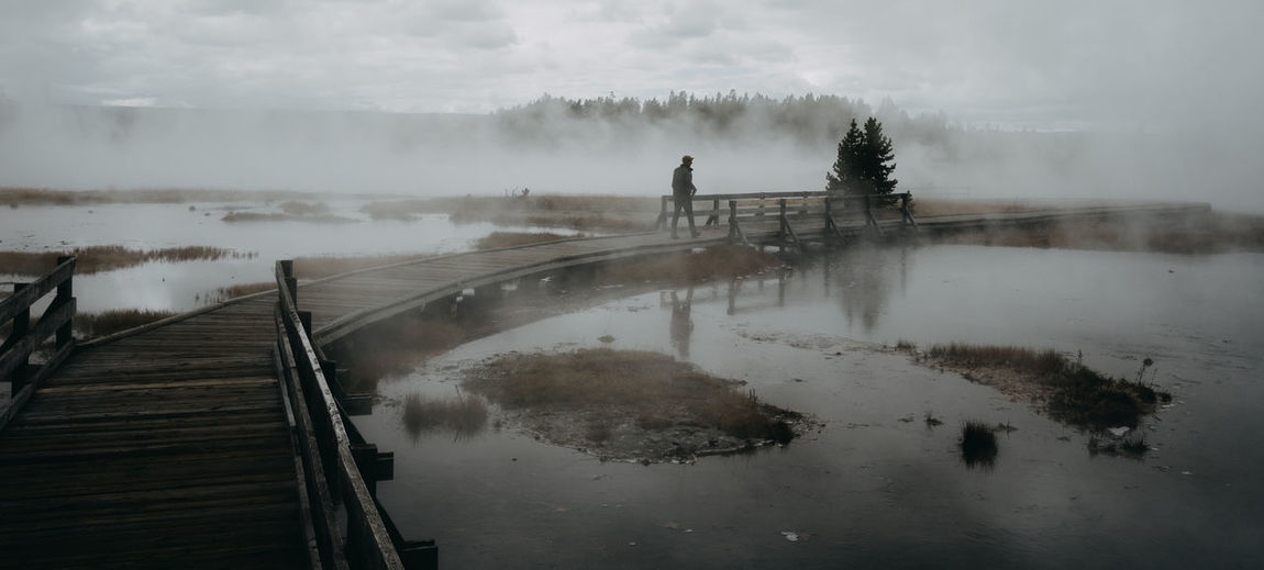 Wyoming Wyoming Landscape Yellowstone National Park Yellowstone Geothermal  Geothermal Activity Wooden Trail Water Nature Sky Reflection One Person Fog Standing Steam Tranquility Real People Smoke - Physical Structure Scenics - Nature Beauty In Nature Tranquil Scene Cloud - Sky Men Non-urban Scene Day Outdoors Hot Spring Power In Nature