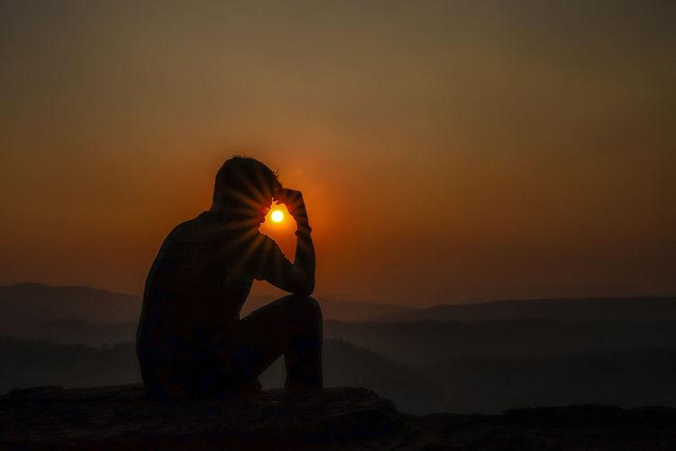 Silhouette man sitting on rock against orange sky