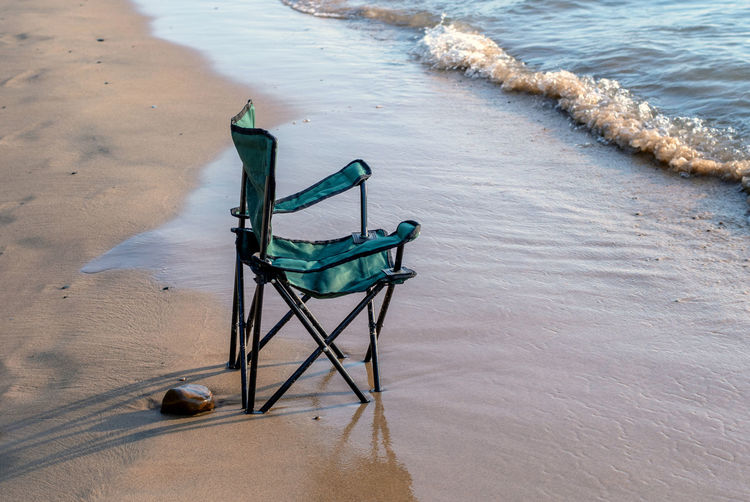 A cloth folding beach chair sits in the wet sand along the shores of lake michigan