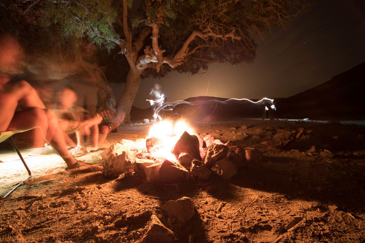 Blurred motion of people sitting by campfire in forest