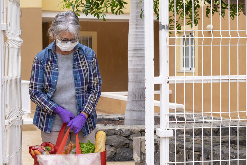 Senior woman wearing mask holding food standing by gate